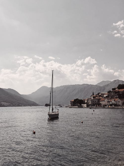 Sailboat floating on calm sea in Bay of Kotor
