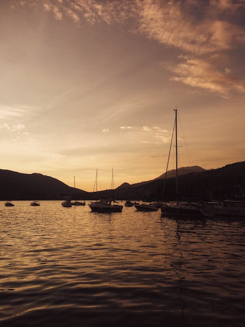 Picturesque scenery of floating boats under sunset sky