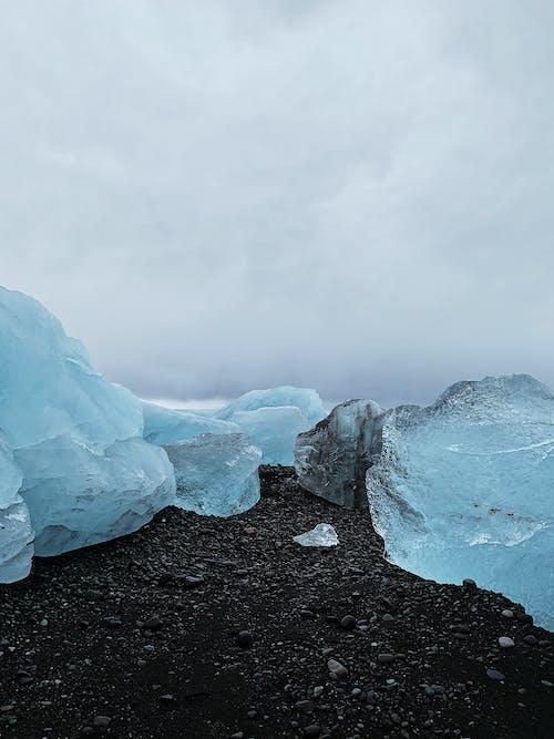 Beautiful crystal blue pieces of iceberg on black volcanic coast of Atlantic Ocean against cloudy sky