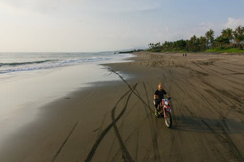 Distant view of adult man in black outfit riding motorbike along seashore while making tracks on wet sand during active travel and tourism