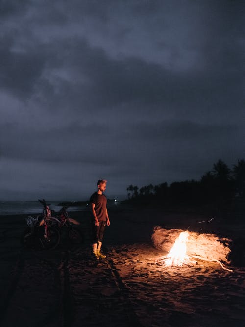 Man and Woman Standing Near Bonfire during Night Time