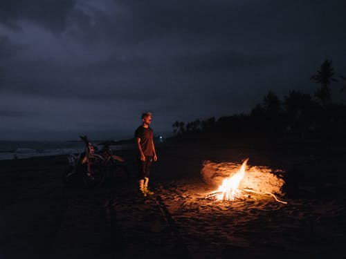 Unrecognizable man with burning fire on beach in night