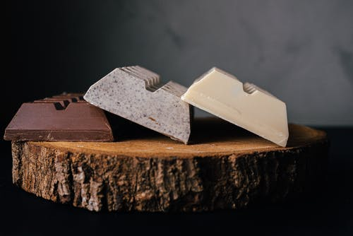 Assorted delicious sweet chocolate bars served on wooden tray against blurred gray background in studio
