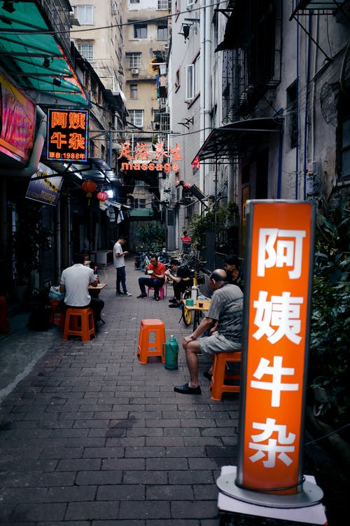 Narrow street between buildings with various street food cafes