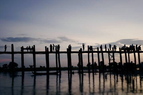 Anonymous people admiring sunset standing on pier
