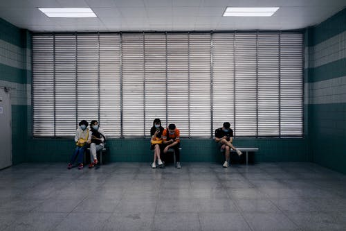 Anonymous people waiting in spacious corridor of medical center