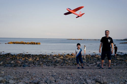 Ethnic father and son launching toy plane on beach at sunset