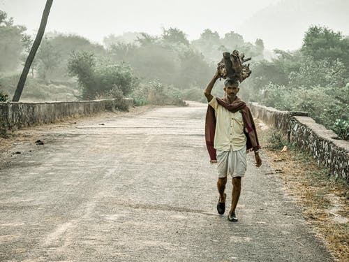 Serious ethnic man walking along path in village with heavy items on head