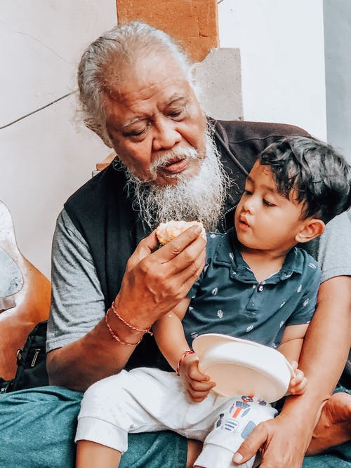 Ethnic bearded grandfather embracing cute child