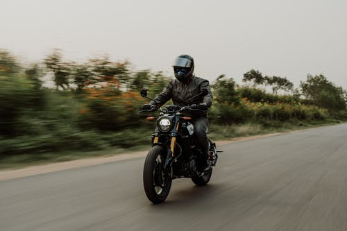 Man in Black Helmet Riding Motorcycle on Road