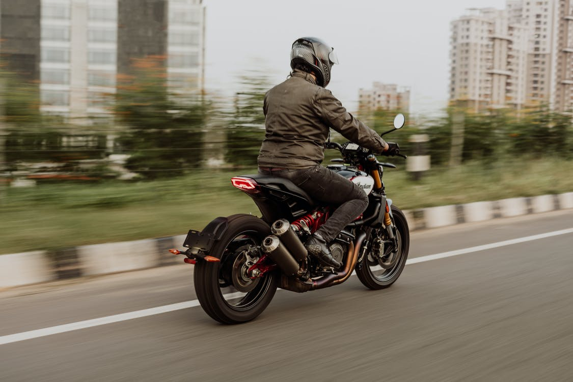Person in Black Jacket Riding on Black Motorcycle on Road