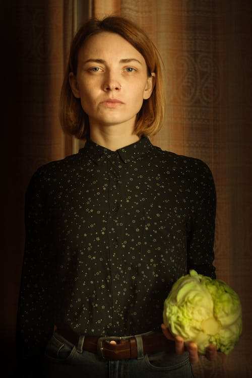 Photo of Woman in Black Long Sleeves Holding Cabbage