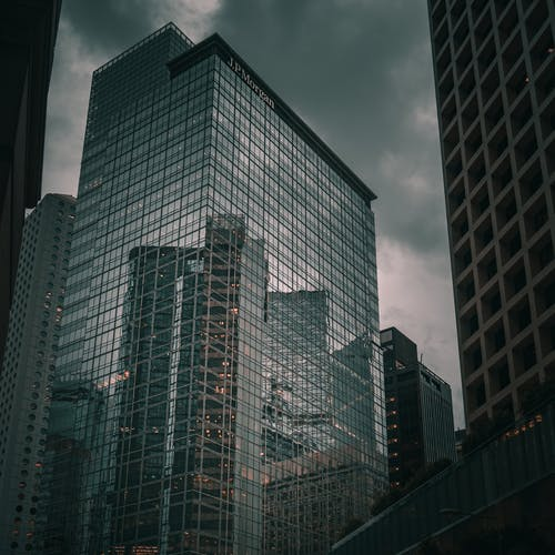 From below of tall commercial skyscraper with glass mirrored walls reflecting modern buildings of downtown against gray cloudy sky