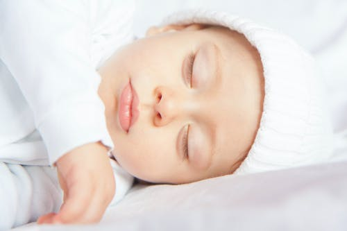 Baby in White Long Sleeve Shirt Lying on White Textile