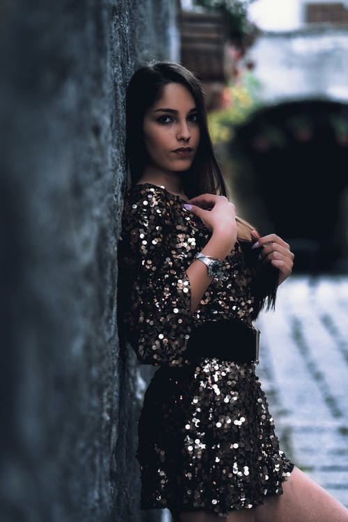 Photo of Woman in Black Sequin Dress Leaning on Wall