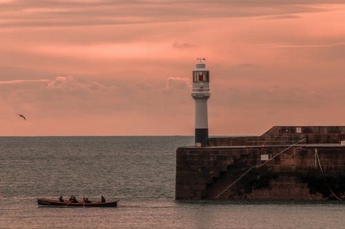 Boat with unrecognizable tourists on sea near lighthouse at sunset