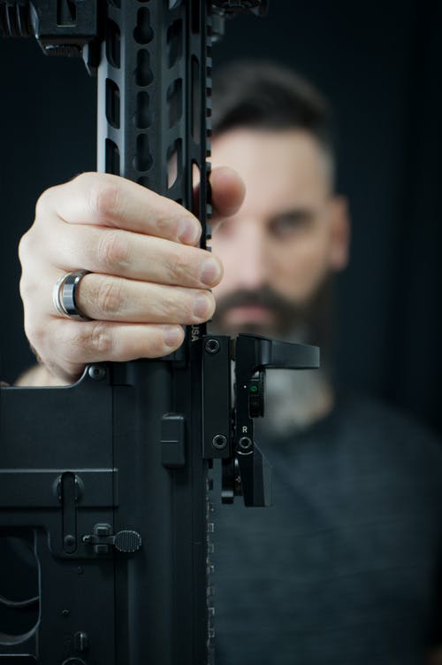 Soft focus of front part of big black gun in hand of anonymous pensive male with beard on blurred background