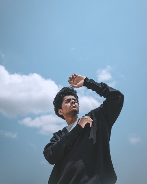 Photo of Man in Black Sweater Against Blue Sky