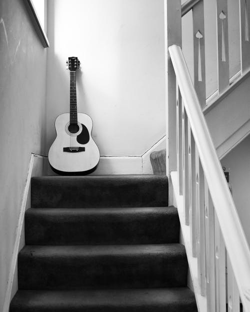Grayscale Photo of Acoustic Guitar on Staircase