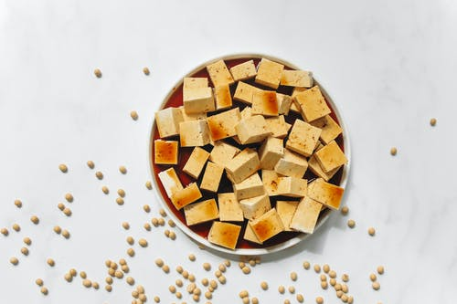 Sliced Tofu with Brown Liquid on White Ceramic Plate