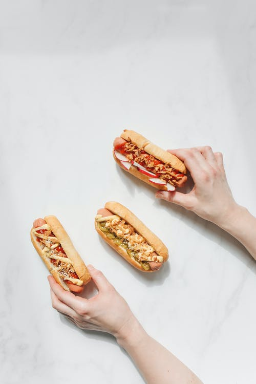 Person Holding Hotdog Sandwiches