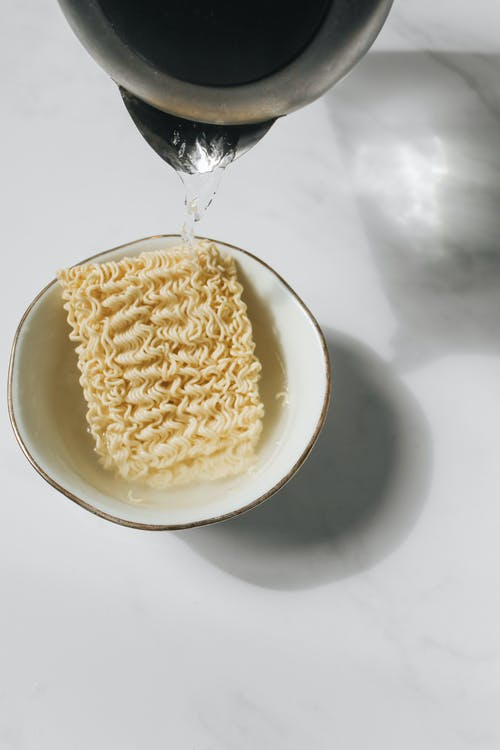 Photo of Pitcher Pouring Hot Water on Bowl With Uncooked Noodles