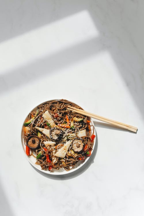 Photo of Noodle Dish and Chopstick on White Ceramic Plate