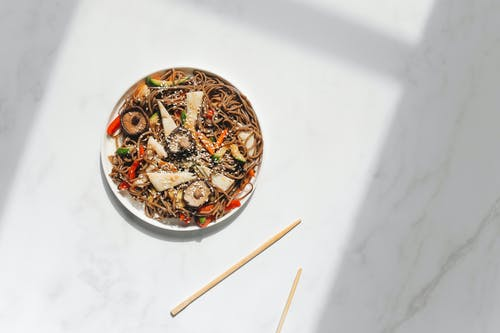 Photo of Noodle Dish on White Ceramic Plate Against White Background