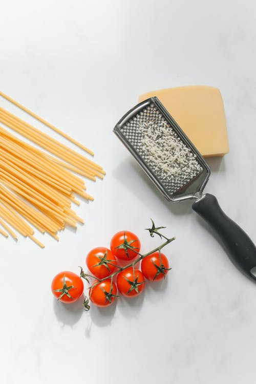 Spaghetti Noodles with Cheese and Tomatoes in a White Background