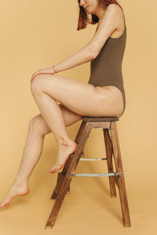 Woman in Black Lingerie Sitting on Brown Wooden Seat