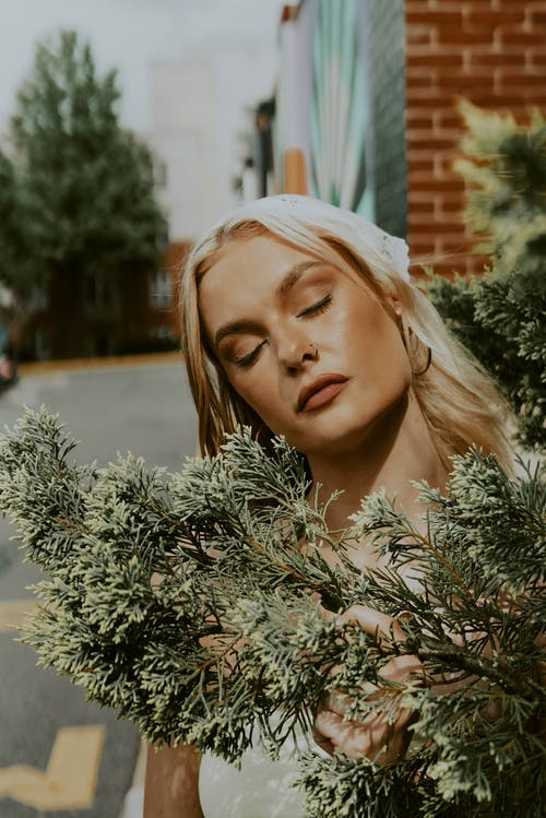 Young dreamy woman behind tree branch