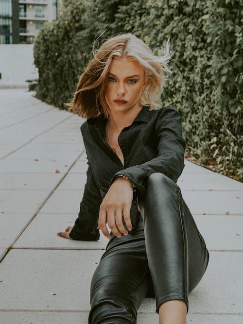Stylish woman in fashionable clothing on ground