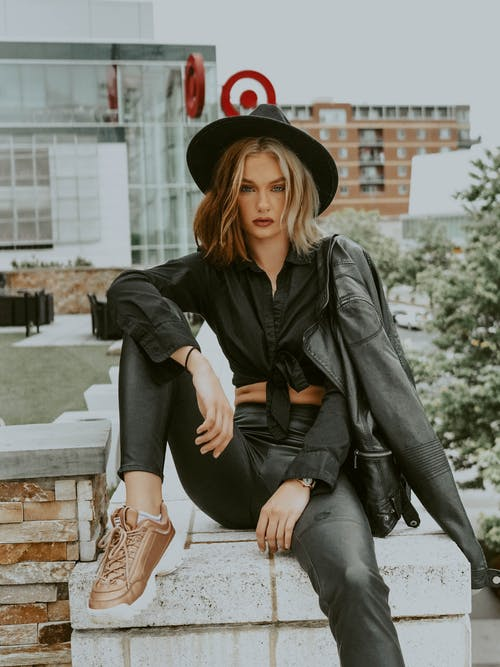Concentrated female in trendy black outfit and hat sitting on stone fence on street