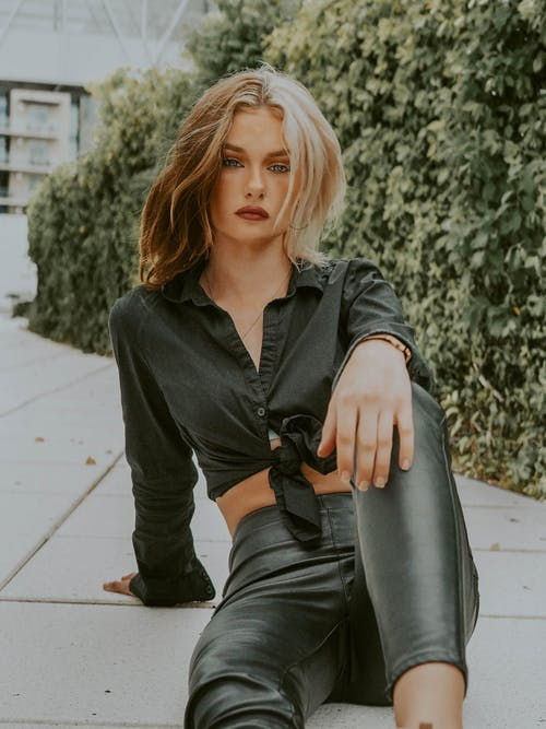 Stylish young female dressed in black outfit sitting on ground against green bushes