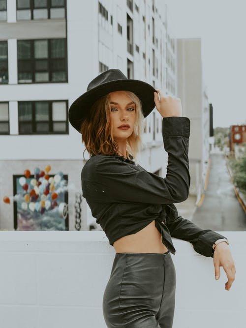 Stylish woman touching hat standing against gray buildings