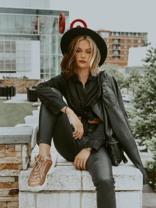 Trendy young female wearing stylish hat and black clothing sitting against high buildings