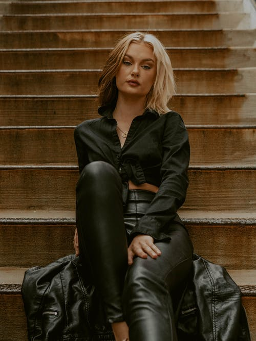 Low angle of confident provocative female in black trendy wear sitting on wooden stairs