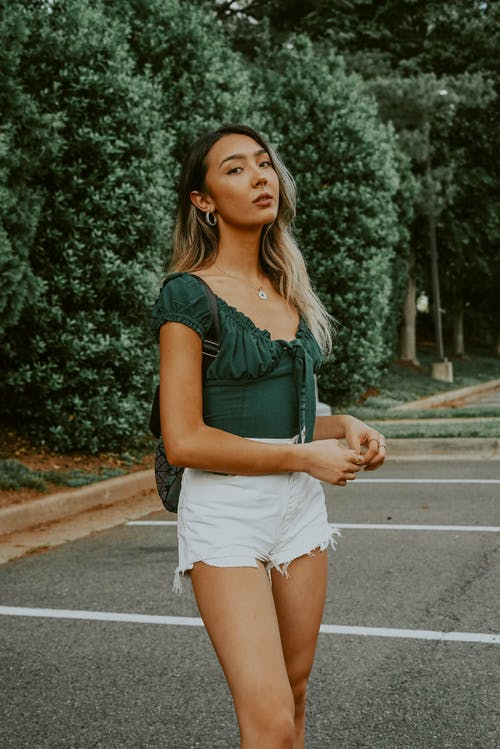 Dreamy Asian young woman in shorts and blouse standing alone against green trees