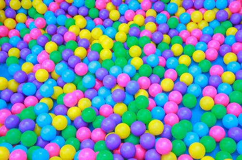From above of colorful plastic balls in dry pool for kids to jump and play in playroom
