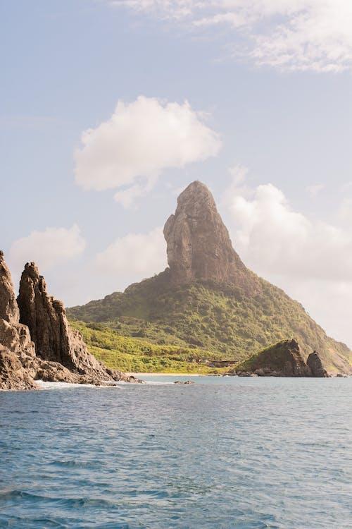 Rocky cliff on coastline of blue sea