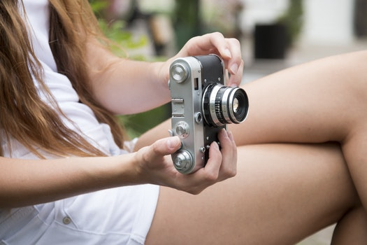 Woman Holding a Gray and Black Adjustable Lens Camera