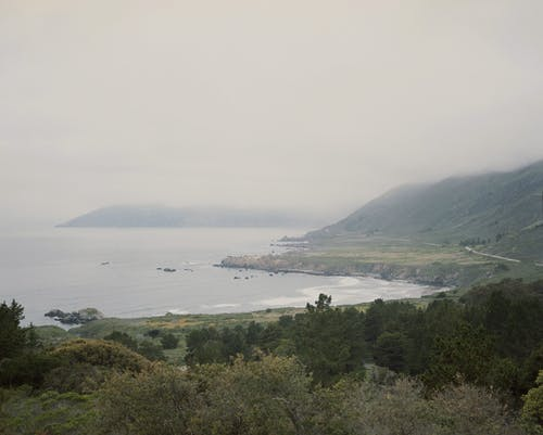 Green mountainous seashore in overcast day