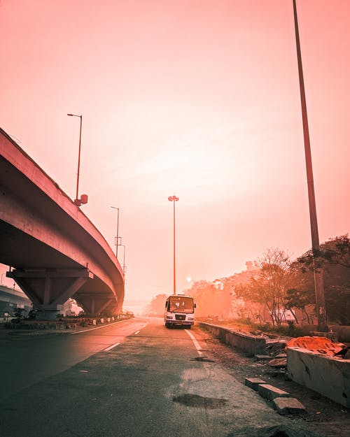 Perspective view of bus driving on empty roadway near cement bridge against cloudless sky during sunset time in summer on street