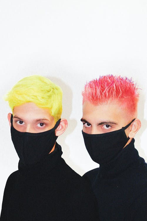 Unrecognizable men with colorful stylish haircuts in medical masks