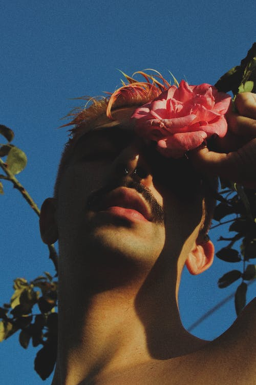 From below of anonymous male with mustache and pierced nose standing with flower in hand under bright sunlight with shadow on face against blue sky