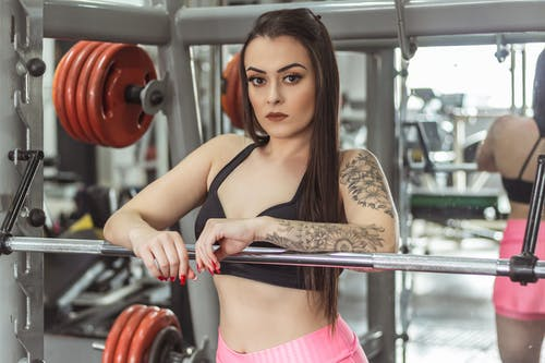 Woman in Pink and White Tank Top Holding Red Dumbbell