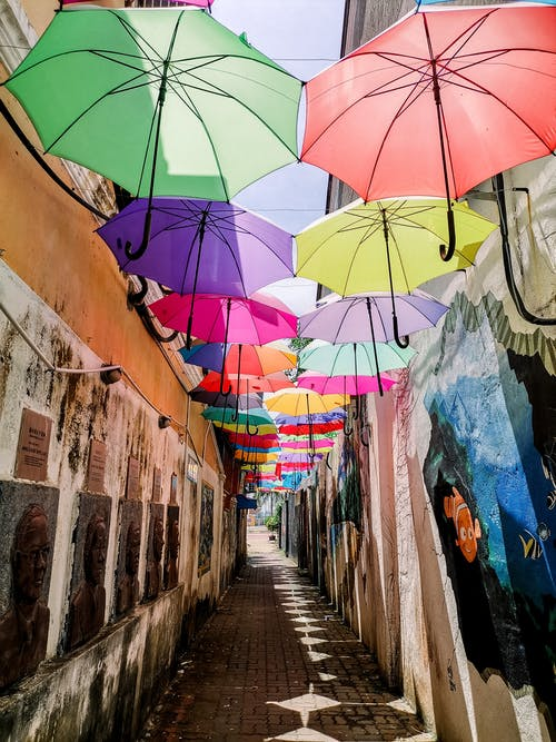 Multicolored umbrellas hanging in air in narrow alley of old street with memorial on wall during daytime in city outside
