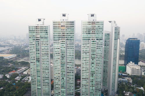 Distance view of contemporary high buildings located near green urban park in megalopolis downtown district against foggy day sky background