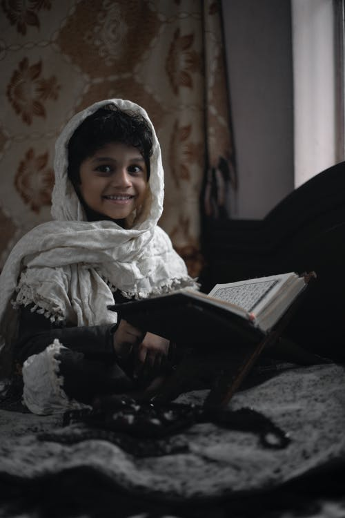 Little ethic child in white blanket sitting on bed in room and reading interesting book while looking at camera during daytime