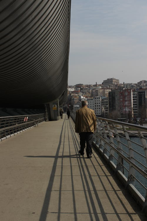 Back view of anonymous man in worn clothes walking across bridge over river in big city at sunny day